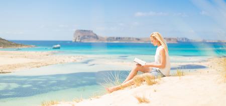 Entspannt Frau genießen Sonne, Freiheit und gutes Buch ein schöner Sandstrand von Balos in Griechenland. Junge Dame, das Lesen, das Gefühl frei und entspannt. Urlaub, Freiheit, Glück, Freude und Wohlbefinden.
