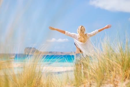 duna: mujer relajada, con los brazos rised, disfrutando del sol, la libertad y la vida de una hermosa playa. Señora joven que se siente libre, relajado y feliz. Concepto de vacaciones, la libertad, la felicidad, el disfrute y el bienestar.