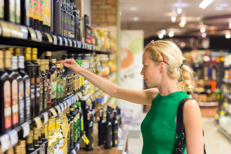 vinegar: Beautiful caucasian woman shopping groceries at supermarket.