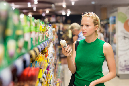 produce departments: Beautiful caucasian woman shopping personal hygiene products at supermarket.
