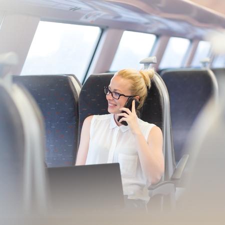 Zakenvrouw praten over mobiel en het werken op de laptop tijdens het reizen met de trein. Zakenreizen concept.