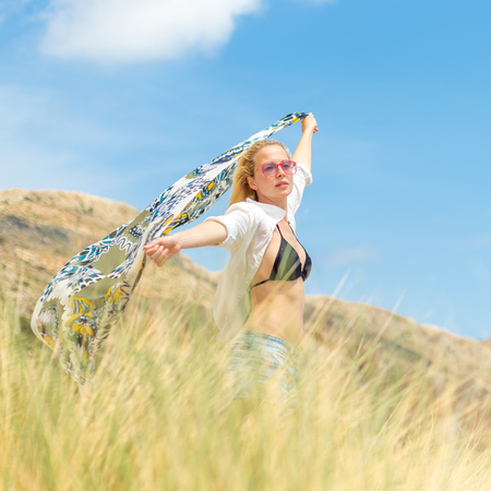 scarf beach: Relaxed woman, arms rised, holding colorful scarf, enjoying sun, freedom and life at beautiful beach. Young lady feeling free, relaxed and happy. Concept of vacations, freedom, joy and well being.