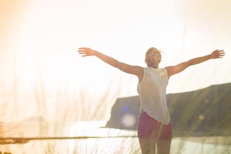 Ontspannen vrouw in wit overhemd, opgeheven armen, genieten van zon, vrijheid en het leven van een prachtig strand. Jonge dame gevoel vrij, ontspannen en gelukkig. Concept van vakantie, vrijheid, geluk, vreugde en welzijn.