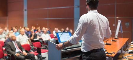 Speaker het geven van een lezing over corporate Business Conference. Publiek bij de conferentiezaal. Business and Entrepreneurship evenement. Panoramisch samenstelling.