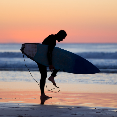 male surfer: Silhouette of male surfer on the beach with the surfboard in sunset.