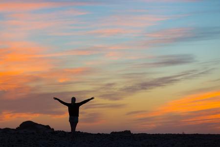 mujer mirando el horizonte: Silueta de la mujer libre que disfruta de la libertad que siente feliz al atardecer. mujer que se relaja en la serena felicidad pura y disfrute eufórico con los brazos levantados extendidos hacia arriba. Foto de archivo