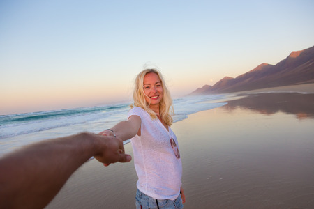 Young romantic couple, holding hands, having fun on perfect deserted beach at sunset. Shot from boyfrieds perspective. Guy looking at her beautiful carefree girlfriend.