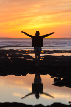 elated: Silhouette of free woman enjoying freedom feeling happy at beach at sunset. Serene relaxing woman in pure happiness and elated enjoyment with arms raised outstretched up.