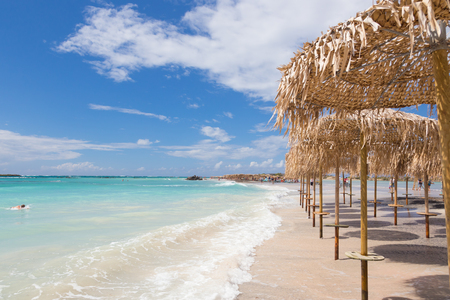 paradise beach: Straw sunshades at Elafonissi beach on Crete island, Greece.