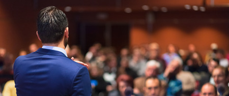 Rear view of speaker giving a talk on corporate Business Conference. Audience at the conference hall. Business and Entrepreneurship event. Panoramic composition. Stok Fotoğraf - 61866696