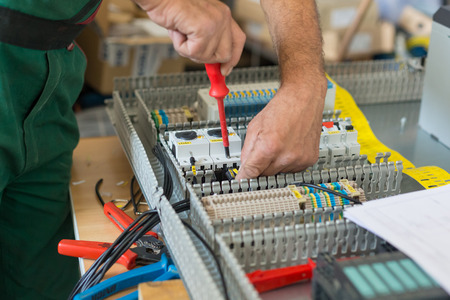 Electrician assembling industrial electric cabinet in workshop. Banque d'images