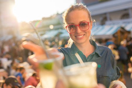 Beautiful young girl toasting outdoors on Open kitchen street food festival in Ljubljana, Slovenia. Popular summer urban tourist event in capital. Archivio Fotografico