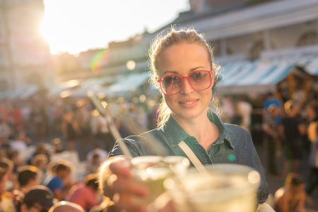 Beautiful young girl toasting outdoors on Open kitchen street food festival in Ljubljana, Slovenia. Popular summer urban tourist event in capital. 写真素材