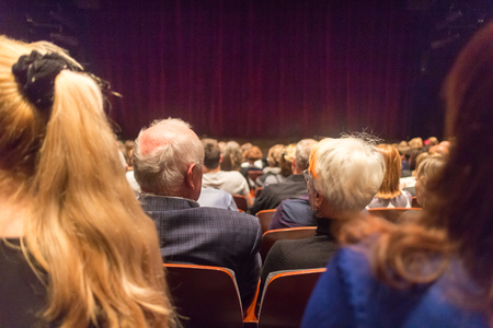 Audience in theathre waiting for drama play to start sen from the rear.