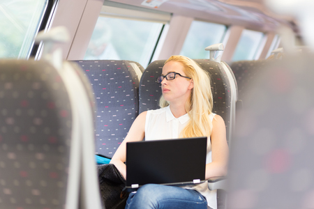 tiresome: Businesswoman naping sitted while traveling by train and working on laptop. Tiresome business travel. Stock Photo