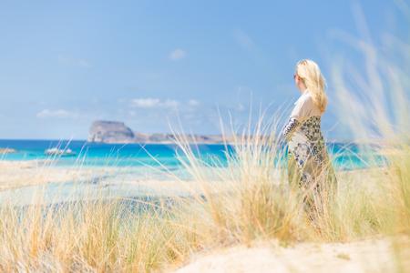 duna: Relajado mujer envuelta en un pañuelo colorido, disfrutando del sol, la libertad y la vida en la hermosa playa de Balos en Grecia. Concepto de vacaciones, vacaciones, libertad, alegría y bienestar.