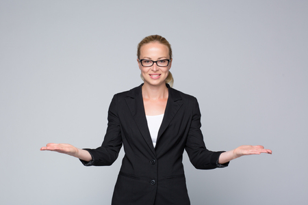 business products: Beautiful young businesswoman smiling, holding open palms with empty copy space. Business woman showing hands sign to sides, concept of advertisement or comparing products. Grey background.