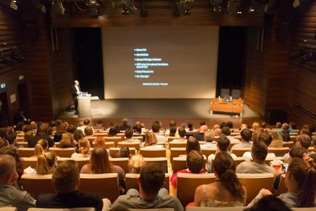 Publiek bij de conferentiezaal. Spreker geeft een lezing in de conferentiezaal op zakelijke evenement. Business and Entrepreneurship concept. Lens focus op mensen in het publiek van achteren.