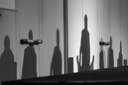 comité d entreprise: Abstract silhouettes of people at business meeting, Seminar event room with dark shadows in background. Leaders in the background business or policy concept. Black and white image. Banque d'images