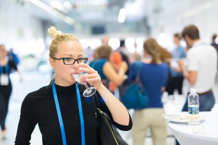 Business woman, wearing name tag, drinking glass of water during coffee break at business meeting or conference. Abstract blurred people socializing n background.