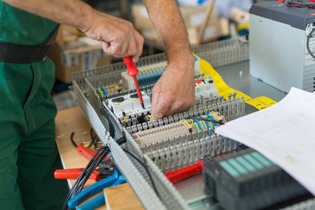 Electrician assembling industrial electric cabinet in workshop. Archivio Fotografico