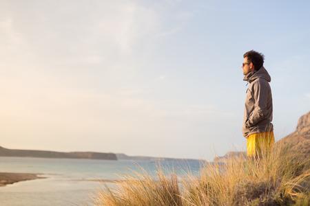 hombre activo deportivo mirando en la distancia, disfrutando de la belleza de la naturaleza, la libertad y la vida, en el precioso paisaje. estilo de vida activo al aire libre.