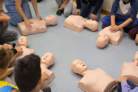 First aid cardiopulmonary resuscitation course in primary school. Kids practicing on resuscitation dolls. 免版税图像