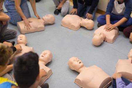 First aid cardiopulmonary resuscitation course in primary school. Kids practicing on resuscitation dolls. Archivio Fotografico