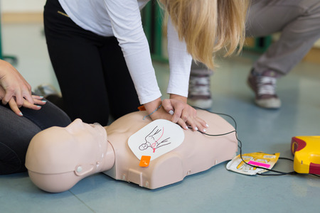 First aid cardiopulmonary resuscitation course using automated external defibrillator device, AED. Banco de Imagens - 65018120