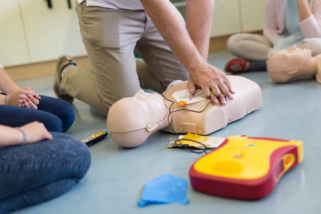 Primer curso reanimación cardiopulmonar ayuda según automatizado dispositivo desfibrilador externo, AED. Foto de archivo