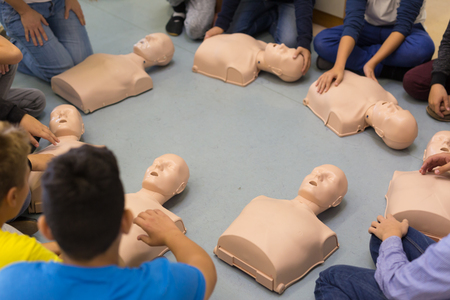 defibrillator: First aid cardiopulmonary resuscitation course in primary school. Kids practicing on resuscitation dolls. Stock Photo