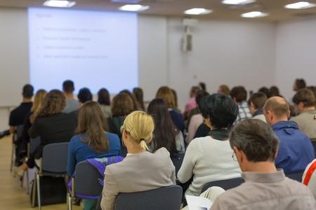 orador: Altavoz dar una charla en la reunión de negocios. Audiencia en la sala de conferencias. Y Creación de Empresas. Centrarse en las personas irreconocibles desde la parte posterior.