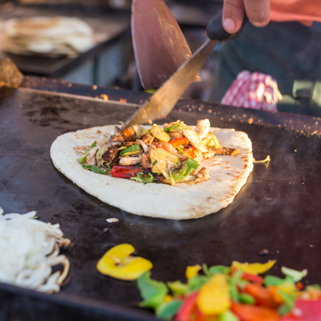 chef kitchen: Chef making chicken with grilled vegetable tortilla wrap outdoor on street stall on Open kitchen international food festival event. Street food ready to serve on a food stall. Stock Photo