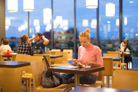restaurant dining: Young female traveler eating pizza at airport restaurant while waiting for late night flight departure. Stock Photo