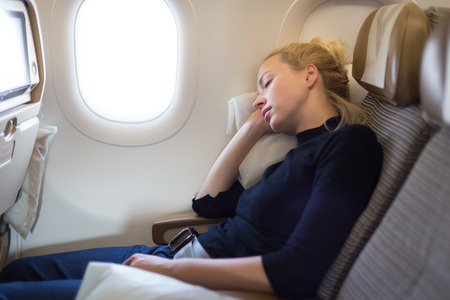 Tired blonde casual caucasian lady napping on seat while traveling by airplane. Commercial transportation by planes. Stockfoto