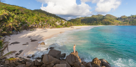 banyan tree: Woman in bikini enjoying beautiful view of Ance Intendance paradice beach from perfect round rocks on Mahe Island, Seychelles. Summer vacations on picture perfect tropical beach concept.
