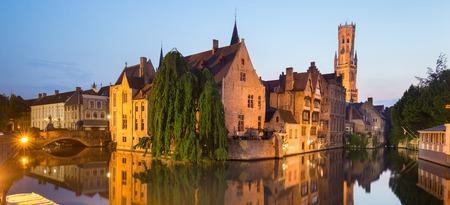 belfort: Panorama of Bruges, Belgium. Image with Rozenhoedkaai in Brugge, Dijver river canal and Belfort, Belfry, tower in twilight. Stock Photo