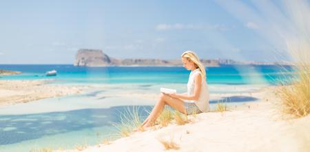 Relaxed woman enjoying sun, freedom and good book an beautiful sandy beach of Balos in Greece. Young lady reading, feeling free and relaxed. Vacations, freedom, happiness, enjoyment and well being. Archivio Fotografico