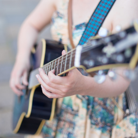 Female street musician playing guitar on sidewalk. Stock Photo