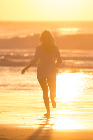 Happy woman enjoying isummer, running joyfully on beach in sunset.