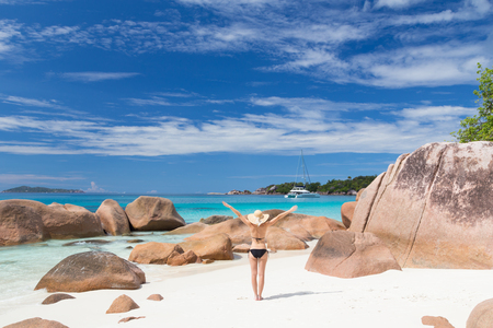 Woman arms rised, wearing black bikini and beach hat, enjoying amazing view on Anse Lazio beach on Praslin Island, Seychelles. Summer vacations on picture perfect tropical beach concept. Stock Photo