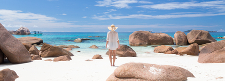 view woman: Woman wearing white loose tunic over bikini and beach hat on Anse Lazio beach on Praslin Island, Seychelles. Summer vacations on picture perfect tropical beach concept.
