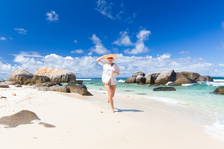 mujeres corriendo: Happy woman wearing white loose tunic over bikini and beach hat, enjoying amazing white sandy beach on Mahe Island, Seychelles. Summer vacations on picture perfect tropical beach concept.