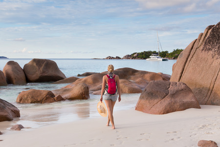 smal: Woman wearing smal backpack, scarf, jeans shorts and beach hat, enjoying view of Anse Lazio beach on Praslin Island, Seychelles. Summer vacations on picture perfect tropical beach concept.