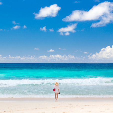 Woman wearing white tunic and beach hat, enjoying amazing view of Police Bay on Mahe Island, Seychelles. Summer vacations on picture perfect tropical beach concept. Stock Photo
