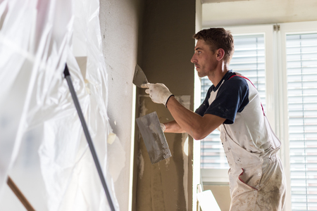 plasterer: Thirty years old manual worker with wall plastering tools renovating house. Plasterer renovating indoor walls and ceilings with float and plaster. Stock Photo