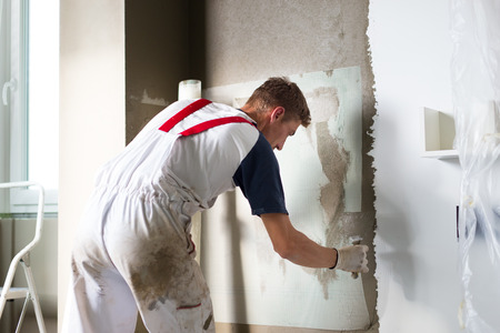 Thirty years old manual worker with wall plastering tools renovating house. Plasterer renovating indoor walls and ceilings with float and plaster. Reklamní fotografie