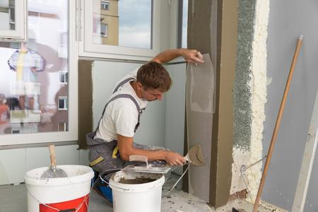 Bouwvakker draagt werknemer overall met muur stukadoors gereedschappen renovatie appartementencomplex. Stukadoor renovatie van binnenmuren en plafonds met vlotter en gips. Bouw afwerking.