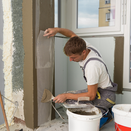 finishing: Construction worker wearing worker overall with wall plastering tools renovating apartment house. Plasterer renovating indoor walls and ceilings with float and plaster. Construction finishing works.