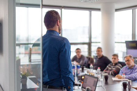 sessions: Business man making a presentation at office. Business executive delivering a presentation to his colleagues during meeting or in-house business training. Rear view. Business and entrepreneurship. Stock Photo
